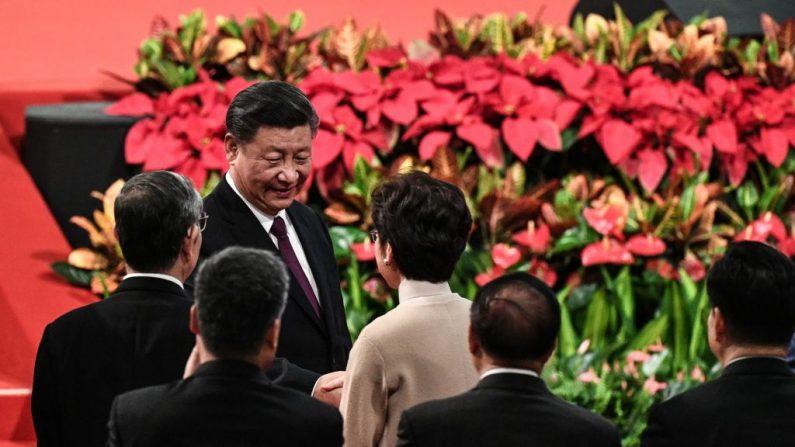 El mandatario chino Xi Jinping estrecha la mano de la jefa ejecutiva de Hong Kong, Carrie Lam, tras pronunciar un discurso durante la ceremonia de nombramiento del nuevo jefe ejecutivo de Macao, Ho Iat-seng, en el marco de las celebraciones del 20º aniversario del retorno de la excolonia portuguesa a China, en Macao, el 20 de diciembre de 2019. (Foto de PHILIP FONG/AFP vía Getty Images)