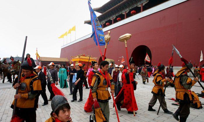 Extras vestidos con trajes en forma de la Dinastía Qing, descansan en un lugar de rodaje de la Base de Locaciones de Cine y Televisión Hengdian el 12 de mayo de 2006 en Dongyang de la Provincia de Zhejiang, China. (Fotos de China / Getty Images)