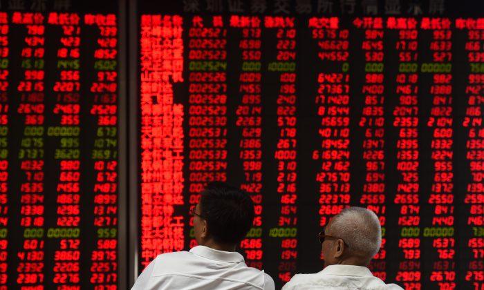 Los inversionistas monitorean los movimientos de los precios de las acciones de una compañía de valores en Beijing el 15 de junio de 2016. (Greg Baker/AFP/Getty Images)