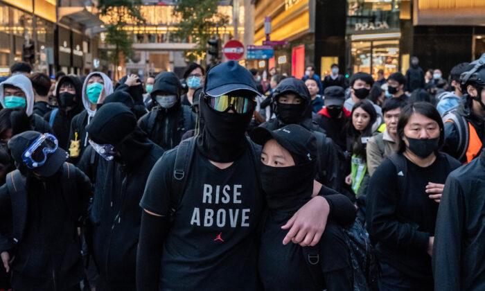 Manifestantes forman una línea de frente durante un enfrentamiento con la policía en una protesta en Hong Kong el 8 de diciembre de 2019. (Anthony Kwan/Getty Images)