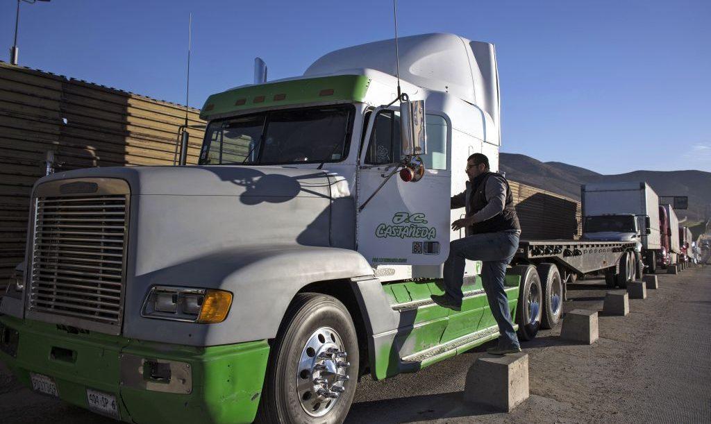 Un conductor se sube a su camión mientras hace fila para cruzar la frontera con los Estados Unidos
