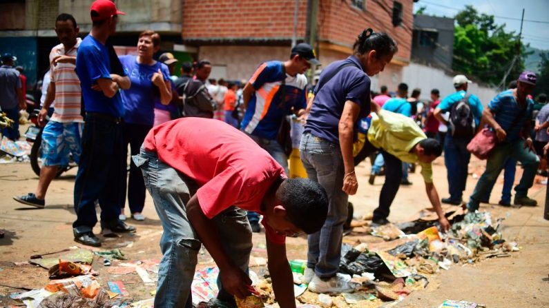 La gente busca comida fuera de un supermercado saqueado en el barrio de El Valle, en Caracas (Venezuela), el 21 de abril de 2017. (Ronaldo Schemidt/AFP/Getty Images)