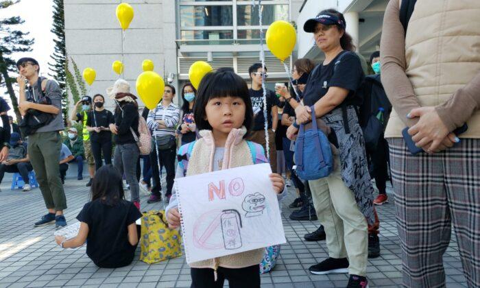 Una niña sostiene un cartel que dice NO al gas lacrimógeno en un acto en Edinburgh Place en Hong Kong, el 1 de diciembre de 2019. (Bill Cox/The Epoch Times)