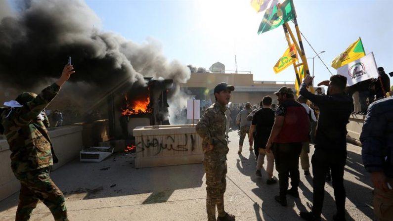 Membros do grupo armado xiita 'Forças de Mobilização Popular' do Iraque e seus apoiadores atacam a entrada da Embaixada dos EUA em Bagdá, Iraque, em 31 de dezembro de 2019. Segundo relatos da mídia, o embaixador dos EUA e outros membros da equipe foram evacuados quando dezenas de pessoas invadiram o complexo da embaixada depois de atear fogo na área de recepção. O ataque na embaixada segue um ataque aéreo mortal dos EUA que matou 25 combatentes da milícia apoiada pelo Irã em 29 de dezembro (EFE / EPA / AHMED JALIL)
