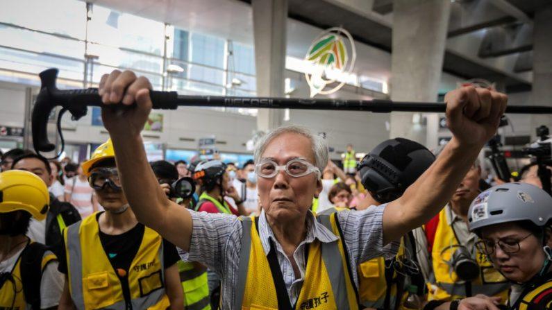 """Esta foto, tomada el 7 de septiembre de 2019, muestra al """"Abuelo Wong"""" (C), de 85 años, protegiendo a los manifestantes de la policía sosteniendo su bastón junto con otros voluntarios de """"cabello plateado"""" en el distrito de Tung Chung en Hong Kong. A pesar de su edad, Wong es un espectador habitual en las batallas callejeras de Hong Kong, cojeando hacia las líneas de la policía, colocándose entre los oficiales antidisturbios y los manifestantes más duros, con la esperanza de desescalar lo que ahora se han convertido en enfrentamientos casi diarios. (Vivek Prakash/AFP vía Getty Images)"""