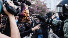 Frente a una pistola, mujer de Hong Kong protesta con un afiche de The Epoch Times contra la policía