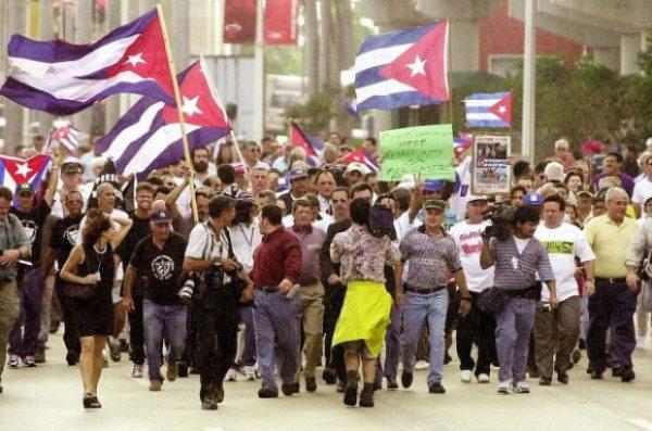 Cubano-americanos agitam bandeiras cubanas enquanto marcham no centro de Miami em 6 de janeiro de 2000 (ROBERTO SCHMIDT / AFP via Getty Images)