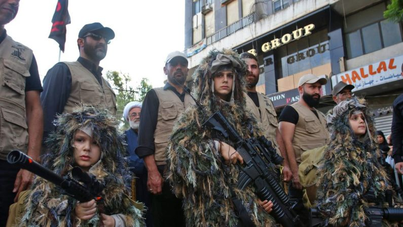 Crianças vestidas com roupas militares carregam armas durante congregação da organização terrorista Hezbollah em 4 de outubro de 2017 (MAHMOUD ZAYYAT / AFP / Getty Images)