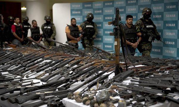 Fuzileiros navais mexicanos escoltam cinco suspeitos de tráfico de drogas do cartel Los Zeta em frente a um lançador de foguetes RPG-7, granadas de mão, armas de fogo, cocaína e uniformes militares apreendidos de suspeitos membros do cartel de drogas e apresentados à imprensa em 9 de junho de 2011 na Secretaria da Marinha na Cidade do México (YURI CORTEZ / AFP via Getty Images)