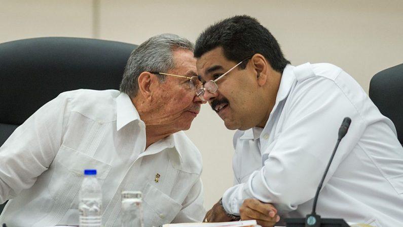 Líder comunista cubano Raúl Castro (esq.) e seu colega chavista venezuelano Nicolás Maduro (dir.) conversam durante a Cúpula Especial da ALBA sobre Ebola em Havana em 20 de outubro de 2014 (YAMIL LAGE/AFP /Getty Images)