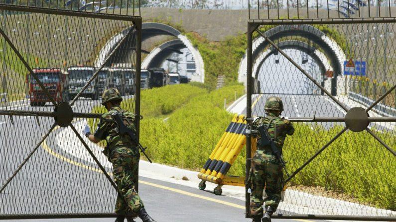 Soldados sul-coreanos abrem portões para permitir a passagem de caminhões sul-coreanos que transportam areia da Coreia do Norte na Zona Desmilitarizada, ao sul da fronteira inter-coreana, em 4 de junho de 2004 em Paju, Coreia do Sul. Esta é a primeira entrega de areia da Coreia do Norte através da rota terrestre que liga as duas Coreias, que concordaram com um pacote histórico de redução de tensão na sexta-feira, depois de conversas de alto nível sobre a prevenção de confrontos nas fronteiras, dando uma grande passo para relaxar a última fronteira da Guerra Fria (Chung Sung-Jun / Getty Images)