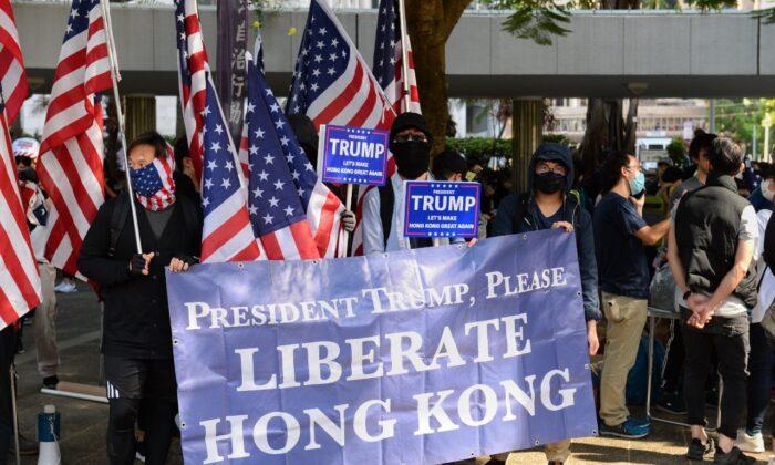Manifestantes levantan una pancarta gigante y banderas de Estados Unidos en un mitin en el Charter Garden de Hong Kong el 1 de diciembre de 2019. (Sun Pi-lung/La Gran Época)