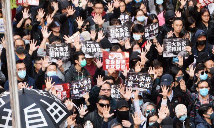 Los manifestantes levantan la mano en señal de reclamo de sus cinco demandas en una marcha en Hong Kong el 8 de diciembre de 2019. (Sung Pi Lung / The Epoch Times)