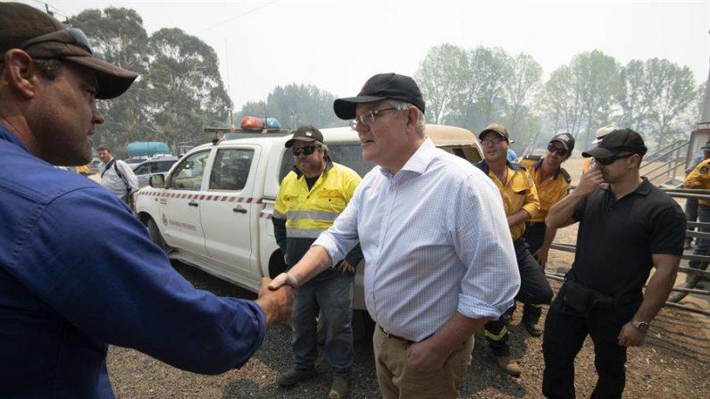 O primeiro ministro australiano Scott Morrison (c) visita hoje algumas das áreas mais afetadas por incêndios florestais (EFE / EPA / WOLTER PEETERS)
