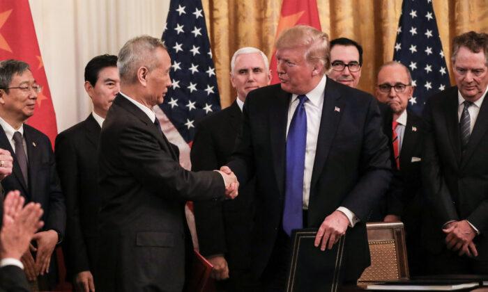 """El viceprimer ministro chino Liu He (izq.) y el presidente de Estados Unidos, Donald Trump, durante la firma de la """"fase uno"""" del acuerdo comercial, rodeado de funcionarios en la Sala Este de la Casa Blanca en Washington el 15 de enero de 2020. (Charlotte Cuthbertson / The La Gran Época"""