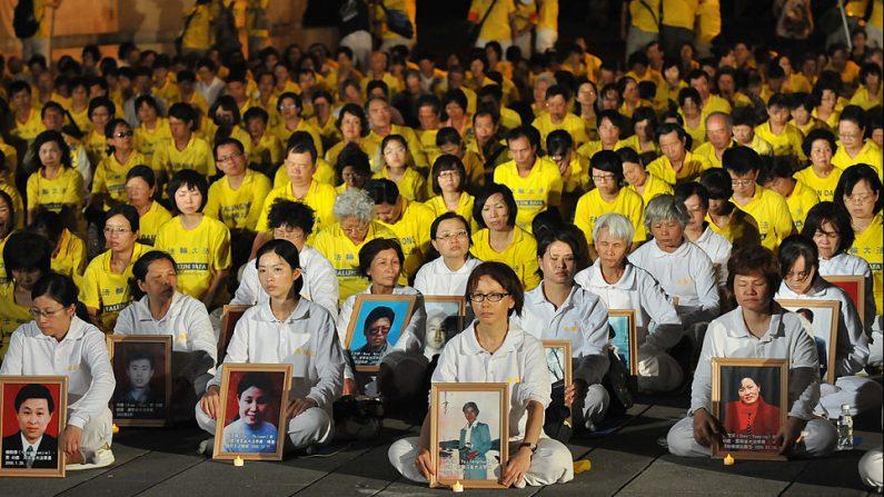 Practicantes de Falun Gong realizan una vigilia ante retratos de las víctimas para protestar en Taipei (Taiwán) el 22 de julio de 2012 contra la persecución de la práctica por parte del Partido Comunista Chino. (Mandy Cheng / AFP / Getty Images)