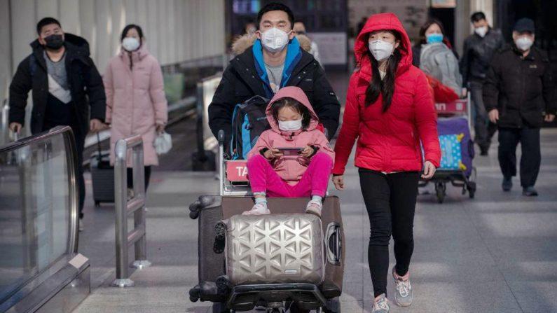 Los pasajeros usan máscaras protectoras mientras caminan con su equipaje en el área de llegadas en el Aeropuerto Capital de Beijing el 30 de enero de 2020 en Beijing, China. (Kevin Frayer / Getty Images)