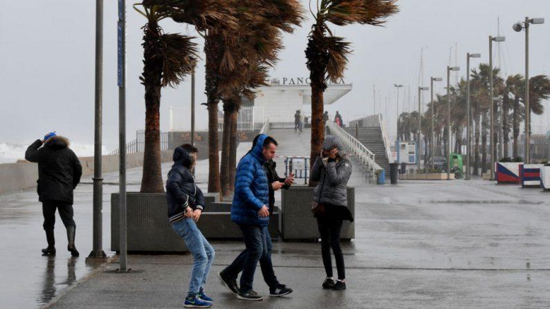Un grupo de personas camina con dificultad debido al fuerte viento en la playa de La Malvarrosa cuando el temporal Gloria azota la costa este española en Valencia el 20 de enero de 2020. (JOSE JORDAN / AFP / Getty Images)