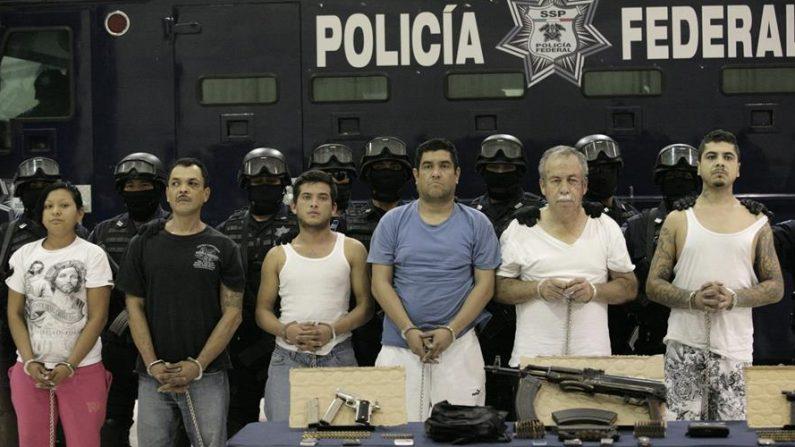Agentes federales resguardan el viernes 9 de diciembre de 2011, a seis presuntos integrantes del Cártel del Golfo, durante una presentación a la prensa en Ciudad de México, tras ser detenidos en un operativo realizado en el municipio de Ciudad Madero, en el estado mexicano de Tamaulipas. EFE/STR