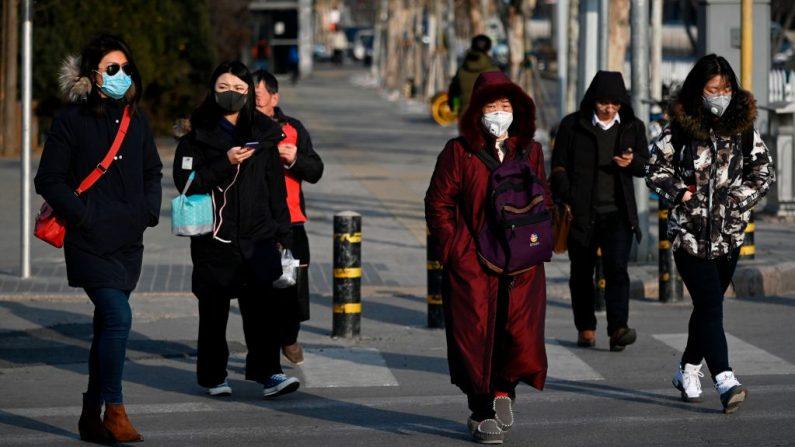 Los peatones con máscaras cruzan una calle en Beijing, China, el 21 de enero de 2020. (WANG ZHAO / AFP / Getty Images)