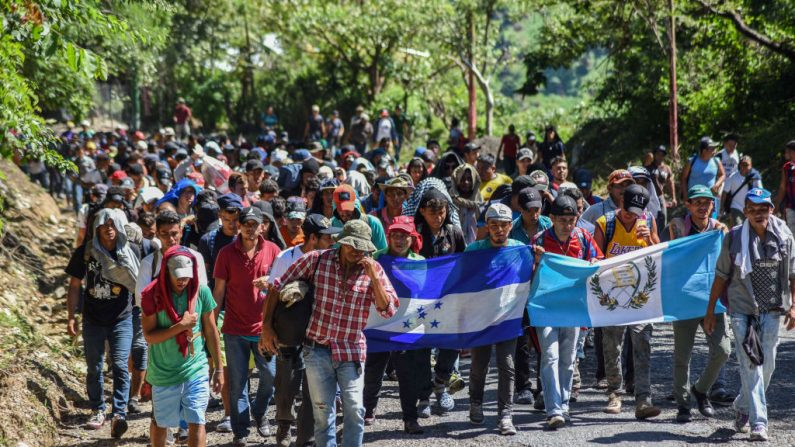 Inmigrantes hondureños participan en una nueva caravana que se dirige a EE.UU. con banderas nacionales hondureñas y guatemaltecas en Quezaltepeque, Chiquimula, Guatemala, el 22 de octubre de 2018. (ORLANDO ESTRADA/AFP a través de Getty Images)