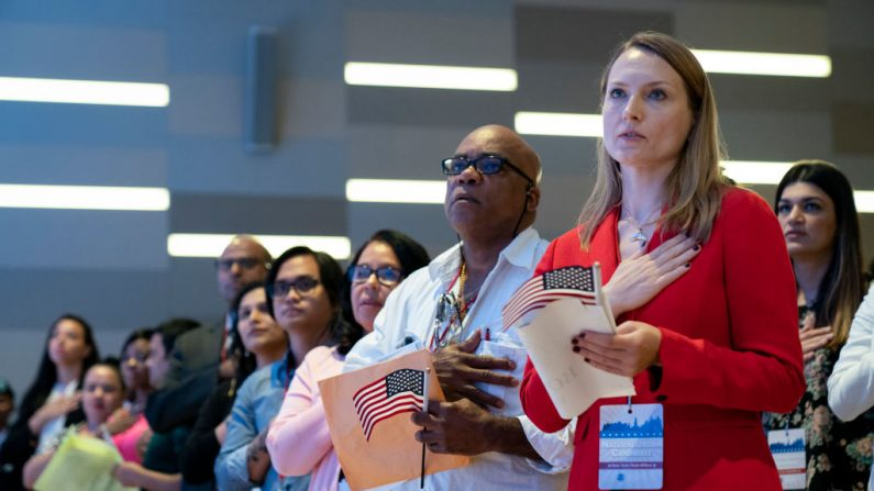 Los nuevos ciudadanos de EE.UU. se ponen de pie para el Juramento de Lealtad durante una ceremonia de naturalización dentro Museo del 11-S el 2 de julio de 2019 en la ciudad de Nueva York. (Drew Angerer/Getty Images)