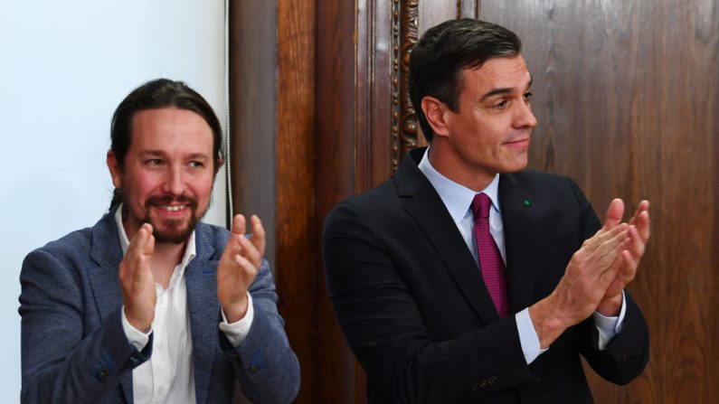 El líder del partido de extrema izquierda Podemos, Pablo Iglesias (iz) y el primer ministro provisional español y candidato a la reelección, el socialista Pedro Sánchez, aplaude después de firmar su acuerdo de gobierno de coalición en el Congreso de Madrid el 30 de diciembre de 2019. (GABRIEL BOUYS / AFP a través de Getty Images)