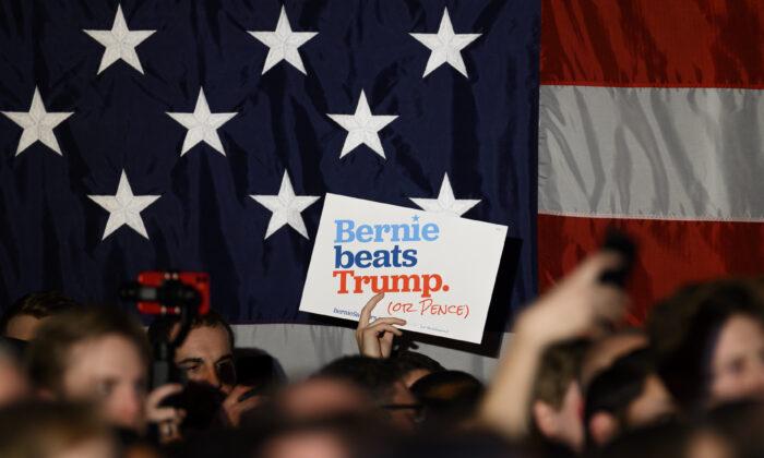 Los partidarios agitan carteles y sostienen sus teléfonos mientras el candidato presidencial demócrata, el senador Bernie Sanders (I-VT), habla en un evento de campaña de Nochevieja el 31 de diciembre de 2019 en Des Moines, Iowa. (Stephen Maturen / Getty Images)