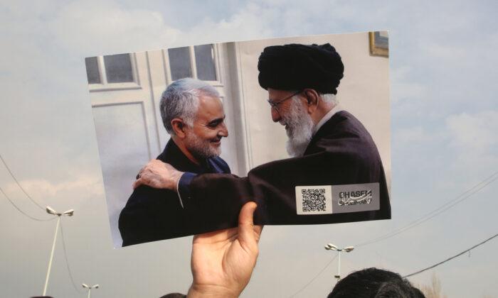 Un hombre sostiene una foto del líder supremo de Irán, el ayatolá Alí Jamenei (Der), con el comandante en jefe de la Guardia Revolucionaria de Irán, Qassem Soleimani, durante una manifestación en Teherán, el 3 de enero de 2020. (Atta Kenare/AFP vía Getty Images)