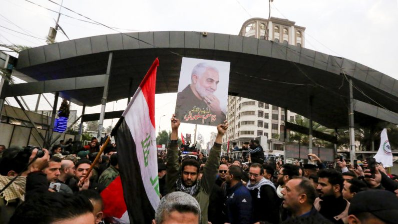 """Manifestantes agitam a bandeira da milícia Hashed al-Shaabi enquanto carregam o retrato do comandante militar iraniano Qasem Soleimani em Kadhimiya, um distrito xiita de Bagdá, em 4 de janeiro de 2020 enquanto cantam """"Death to America"""" em protesto à morte de Soleimani e o chefe paramilitar iraquiano Abu Mahdi al-Muhandis durante um ataque aéreo dos EUA. (SABAH ARAR / AFP via Getty Images)"""