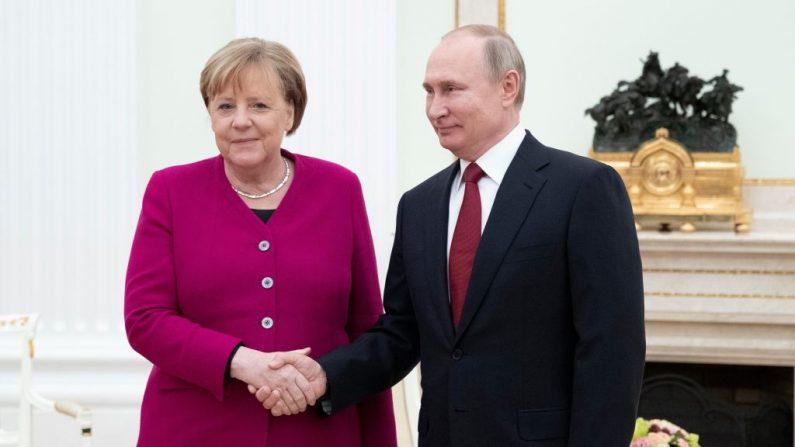 El presidente ruso Vladimir Putin (a la derecha) da la bienvenida y estrecha la mano de la canciller alemana Angela Merkel (a la izquierda) antes de su reunión en el Kremlin de Moscú, el 11 de enero de 2020. (PAVEL GOLOVKIN/POOL/AFP vía Getty Images)