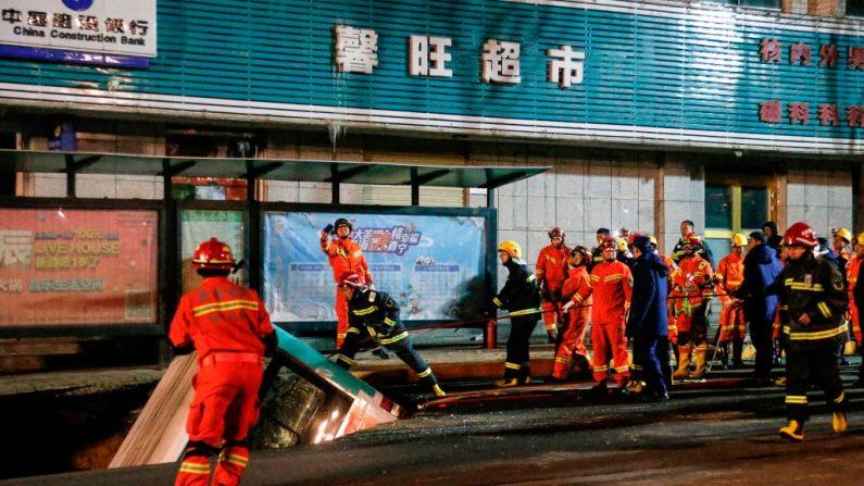 Esta foto tomada el 13 de enero de 2020 muestra a los rescatistas chinos que se preparan para levantar un autobús después de un colapso en Xining, en la provincia de Qinghai, en el noroeste de China. - Un enorme sumidero se tragó a los transeúntes y un autobús público en el noroeste de China, informaron los medios estatales el 14 de enero. (STR / AFP / Getty Images)