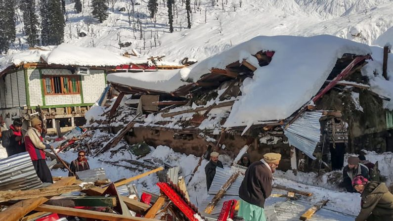 Los residentes locales retiran los escombros de una casa derrumbada luego de fuertes nevadas que desencadenaron una avalancha en el valle de Neelum, en Cachemira, Pakistán el 14 de enero de 2020. (STR / AFP / Getty Images)