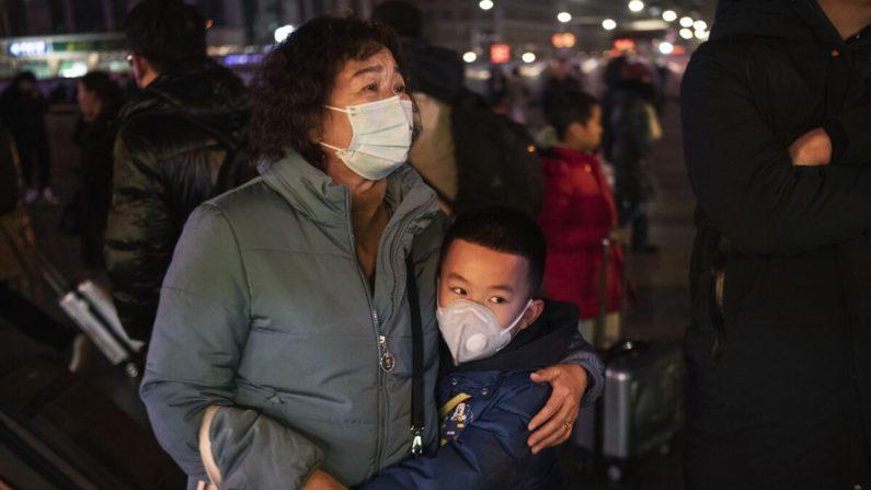 Un niño chino abraza a un pariente cuando sale para abordar un tren en la estación de trenes de Beijing en Beijing, China, el 21 de enero de 2020. (Kevin Frayer/Getty Images)