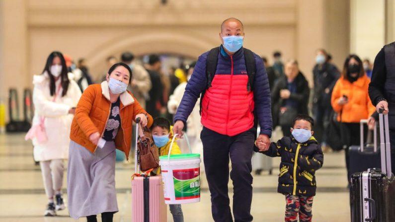 Pasajeros con máscaras faciales caminan por la estación de tren de Hankou en Wuhan, en la provincia central de Hubei en China, el 21 de enero de 2020. (AFP via Getty Images)