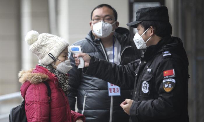 El personal de seguridad comprueba la temperatura de los pasajeros en el muelle del río Yangtsé en la ciudad de Wuhan (provincia de Hubei), China, el 22 de enero de 2020. (Foto de Getty Images)