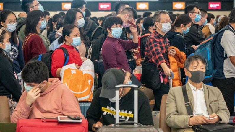 Los viajeros con mascarilla esperan en la sala de embarque de la estación West Kowloon el 23 de enero de 2020 en Hong Kong, China.  (Anthony Kwan / Getty Images)