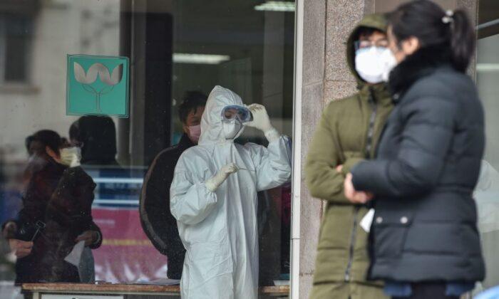 Una enfermera (centro), que lleva ropa protectora para ayudar a detener la propagación de un virus mortal que comenzó en la ciudad, observa un termómetro en el Quinto Hospital de Wuhan el 24 de enero de 2020. (Hector Retamal/AFP vía Getty Images)
