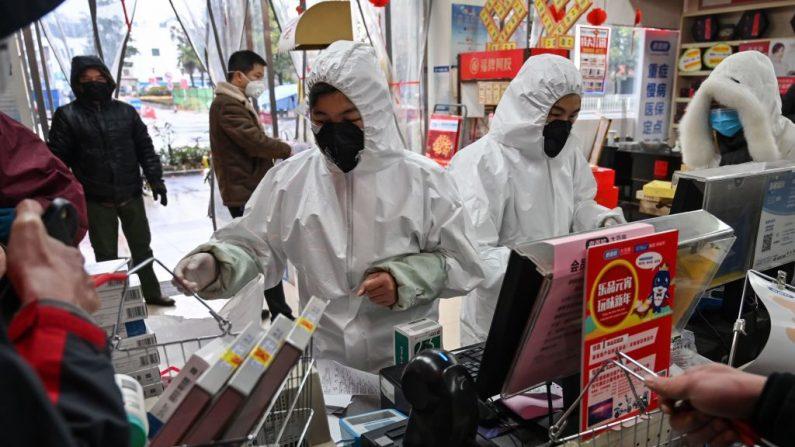 Trabajadores de una farmacia que usan ropa y máscaras de protección atienden a los clientes en Wuhan el 25 de enero de 2020. (Hector Retamal/AFP vía Getty Images)
