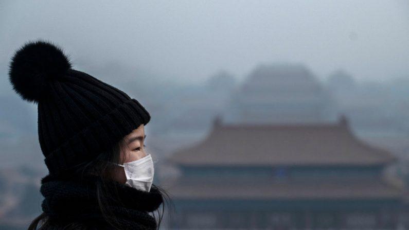 Una niña china usa una máscara protectora mientras se para en un mirador en la Ciudad Prohibida, que fue cerrada por las autoridades, durante el feriado del Año Nuevo Chino el 26 de enero de 2020 en Beijing, China. (Kevin Frayer/Getty Images)