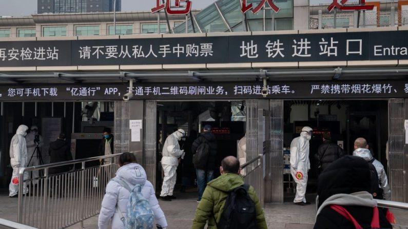 Personal de seguridad lleva ropa protectora para ayudar a detener la propagación del virus mortal que comenzó en Wuhan, comprueba la temperatura de las personas utilizando dispositivos portátiles y una avanzada cámara térmica (izq.) en la entrada de una estación de metro en Beijing el 27 de enero de 2020. (Foto de NICOLAS ASFOURI/AFP vía Getty Images)