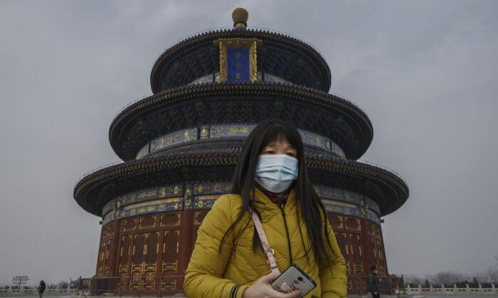 Una visitante china usa una máscara protectora mientras recorre los terrenos del Templo del Cielo en Beijing, China, el 27 de enero de 2020. (Kevin Frayer/Getty Images)