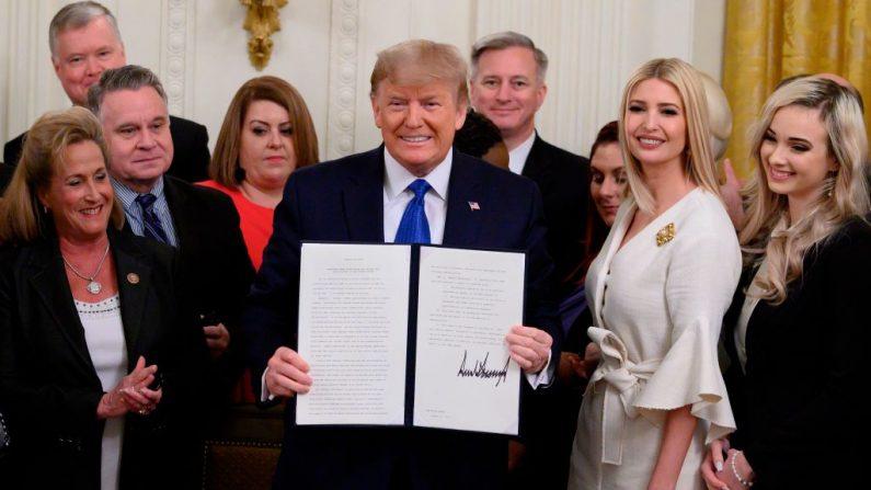 El presidente de los Estados Unidos Donald Trump sostiene una orden ejecutiva sobre la lucha contra la trata de personas junto a Ivanka Trump en la Sala Este de la Casa Blanca en Washington, DC el 31 de enero de 2020. (ANDREW CABALLERO-REYNOLDS/AFP via Getty Images)