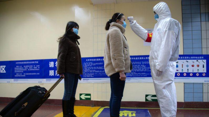 Un trabajador de la salud comprueba la temperatura de las mujeres que entran en el metro el 26 de enero de 2020 en Beijing, China. (Betsy Joles/Getty Images)