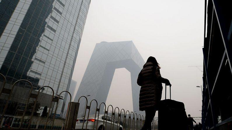 Una mujer pasa por delante de la sede de CCTV en medio de una espesa niebla tóxica en Beijing el 8 de diciembre de 2015. (STR/AFP vía Getty Images)