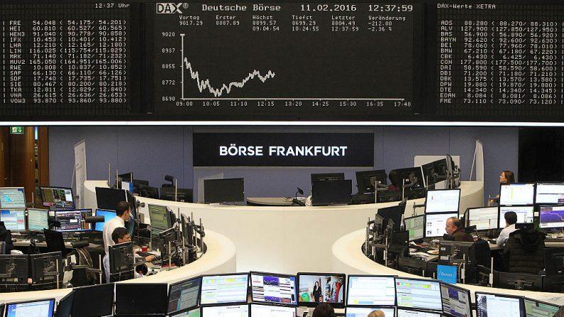 Varios operadores trabajan frente a un tablero que muestra el índice de acciones alemán DAX en la bolsa de valores de Fráncfort (Alemania) el 11 de febrero de 2016. (DANIEL ROLAND/AFP a través de Getty Images)