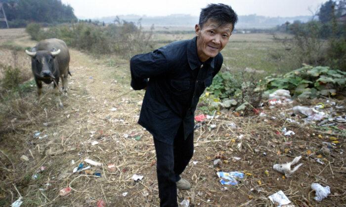 Un agricultor arrastra a su búfalo de agua por senderos llenos de basura en una aldea en las afueras de Yueyang, provincia de Henan, China, el 30 de octubre de 2004. Más de la mitad de los campesinos chinos son tan pobres que no pueden cuidarse a sí mismos. (Frederic J. Brown/AFP vía Getty Images)