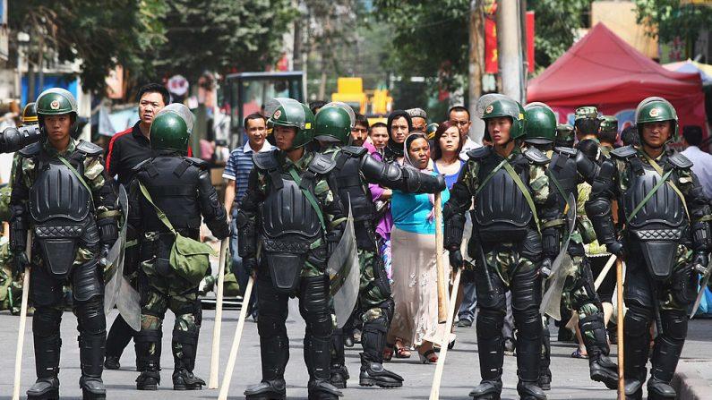 Personas uigures (c) caminan cerca de la policía mientras forman una línea cruzando una calle el 8 de julio de 2009 en Urumqi, la capital de la región autónoma uigur de Xinjiang, China. (Guang Niu / Getty Images)