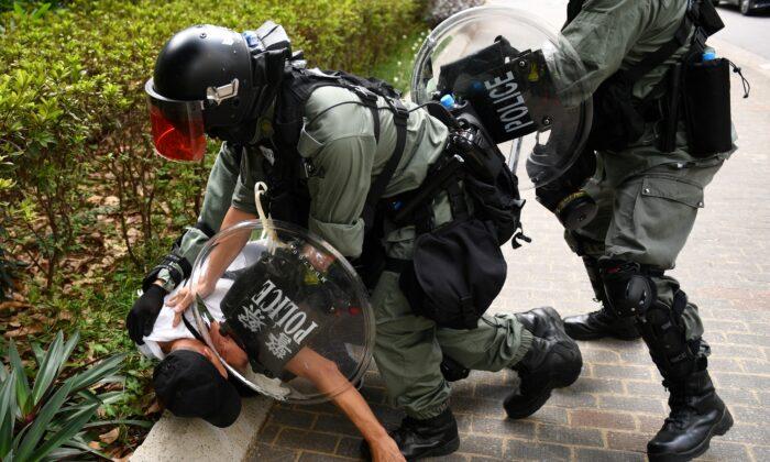 La policía de Hong Kong detiene a un hombre por una razón desconocida frente a un centro comercial en el área de Tai Koo de Hong Kong, China, el 13 de octubre de 2019. (Mohd Rasfan / AFP a través de Getty Images)