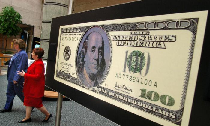 """Dos mujeres no identificadas pasan junto a un billete de 100 dólares en un vídeo durante una visita a la exposición """"Dinero en movimiento"""" en el Banco de la Reserva Federal de Filadelfia en Filadelfia, Pensilvania, el 2 de julio de 2003. (William Thomas Cain/Getty Images)"""